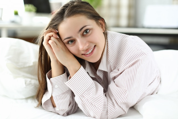 Happy woman in a mans shirt lies on the bed