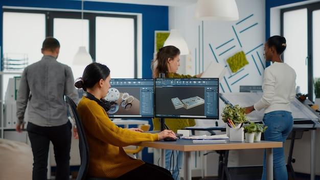 幸せな女性の機械エンジニアは、コンピューターで作業しながら音楽を聴いてヘッドフォンを装着しています...