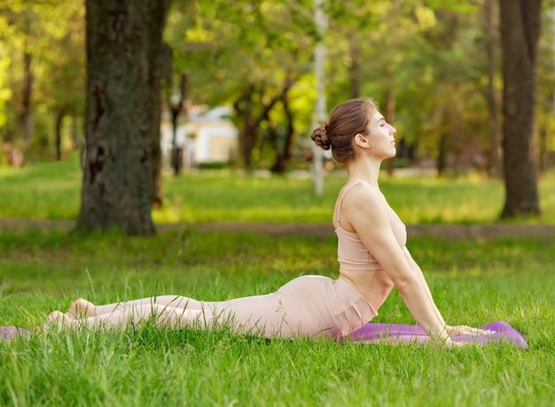 행복 한 여자는 화창한 공원에서 명상. 휴식과 웰빙의 개념