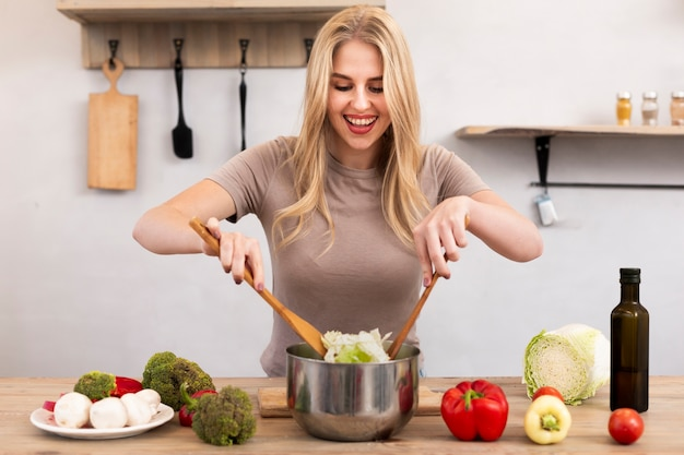Happy woman mixing the bowl with salad