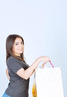 Un modello di donna felice che tiene un sacco di borse della spesa su sfondo bianco.