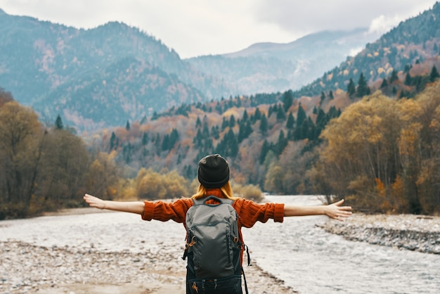 Happy woman in the mountains travels near the river in nature and raised her hands up