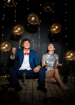 Happy woman near smiling man between tossing balloons