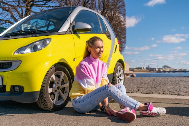 Happy woman near a yellow car in the city