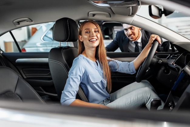 Happy woman new car owner sitting in driver seat and looking around