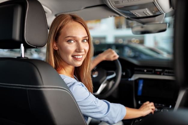 Happy woman in new car sitting in driver seat and looking around