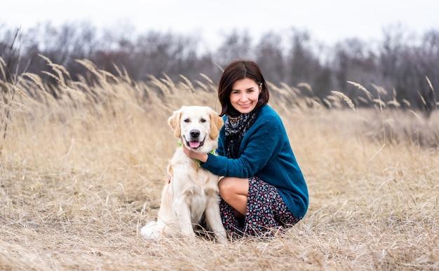 Счастливая женщина рядом с милой молодой собакой на улице