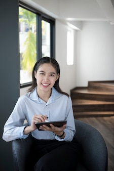 Happy woman office worker holding digital tablet and smiling to camera while sitting in office.