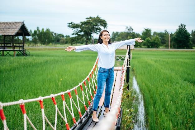 晴れた日に緑の牧草地の木製の橋で幸せな女