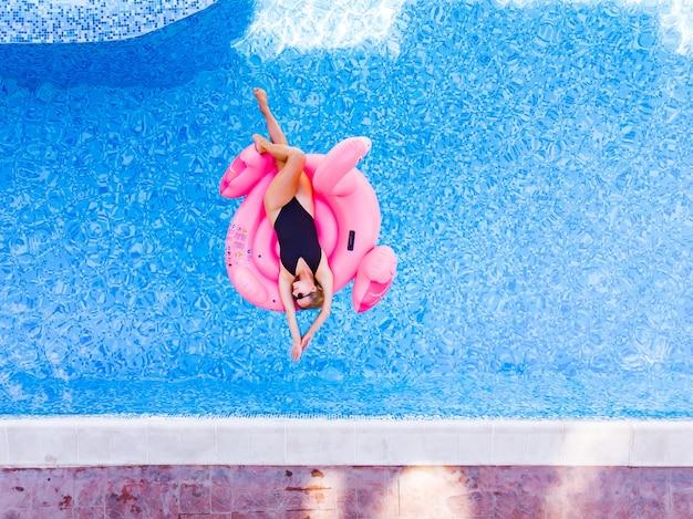 플라밍고 수영장에서 행복한 여성이 수영장에 떠 있고 드론 공중 전망