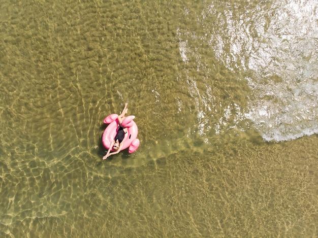 플라밍고 수영장에서 행복한 여자가 바다에 떠 있고 드론 공중 전망