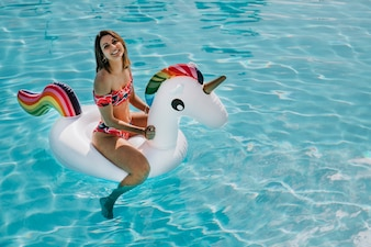 Happy woman on inflatable unicorn in pool