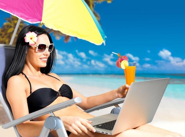 Счастливая женщина на пляже с портативным компьютером.