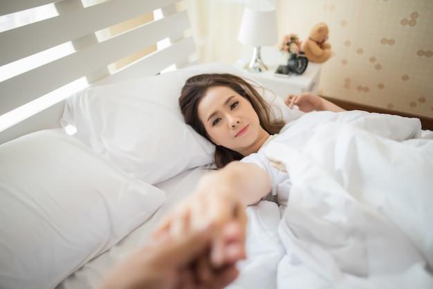 Счастливая женщина на кровати и пригласила своего парня сделать что-то