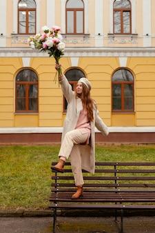야외에서 봄에 꽃의 꽃다발을 들고 벤치에 행복 한 여자