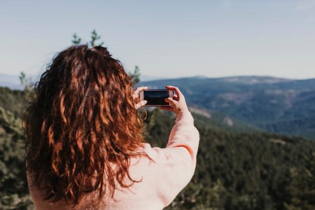 携帯電話で写真を撮る秋の自然の夕日に幸せな女。楽しいアウトドア