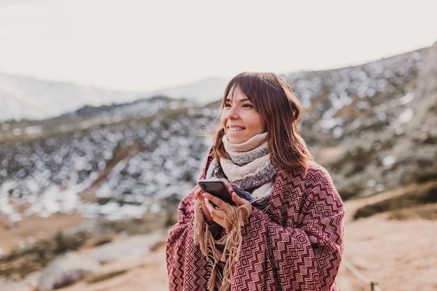 携帯電話を使用して秋の自然の夕日に幸せな女。楽しいアウトドア