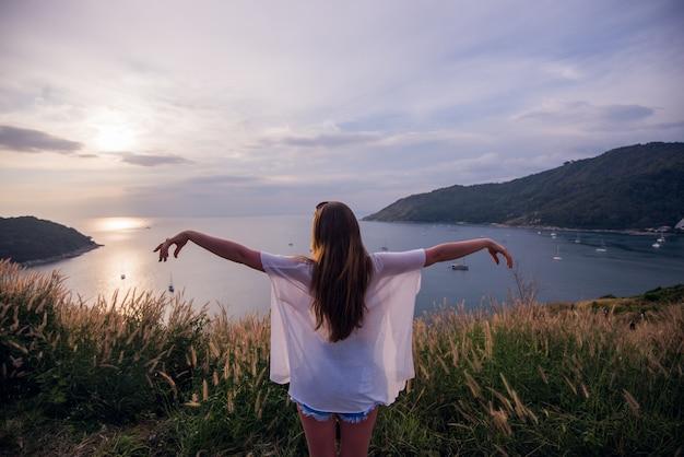両手を広げて夏の自然の夕日に幸せな女