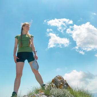 青い空と雲と山の頂上に幸せな女