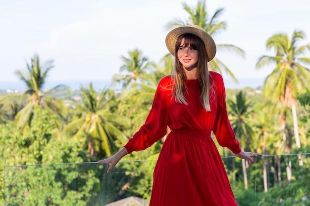 海と梅の木の熱帯の景色を望むバルコニーに赤い夏のドレスと麦わら帽子で休暇中の幸せな女性。