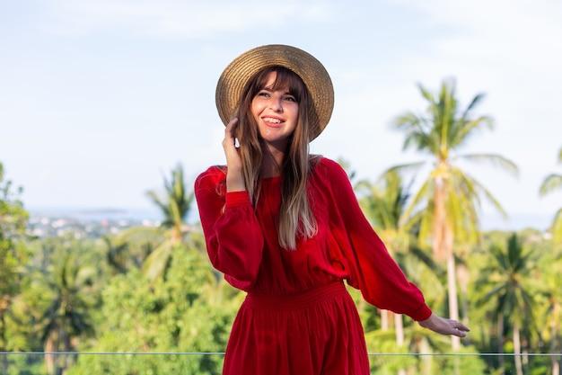 Счастливая женщина в отпуске в красном летнем платье и соломенной шляпе на балконе с тропическим видом на море и сливы.