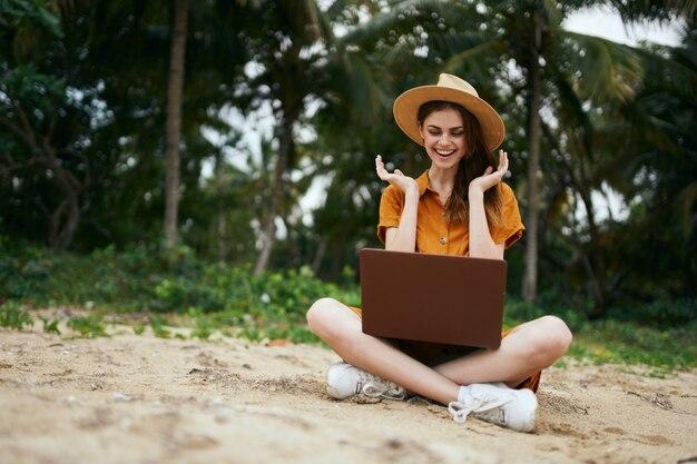 ラップトップで美しいモデルの休暇で幸せな女