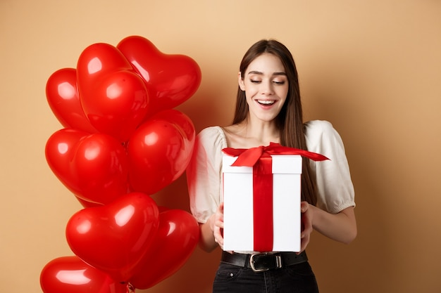 Happy woman open valentines day gift, smiling excited and looking at present box