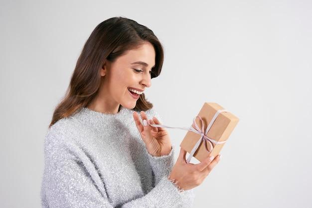 贈り物を開く幸せな女性
