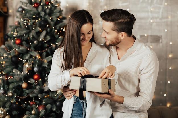 행복 한 여자는 크리스마스 이브에 선물을 엽니 다.