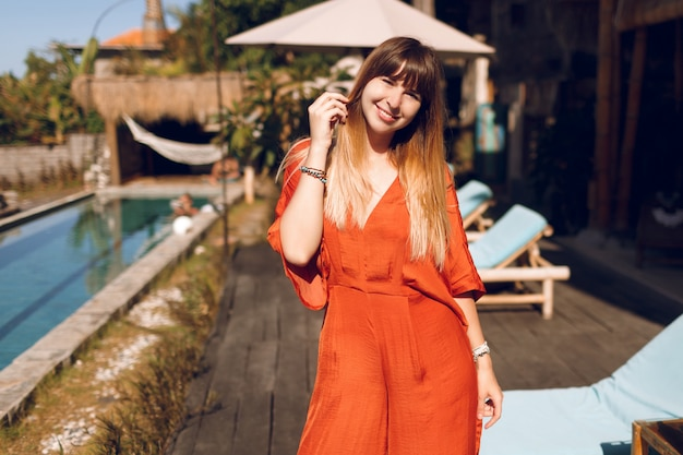 Happy woman in orange dress posing in tropical authentic resort during holidays