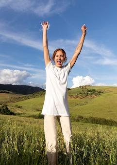 Donna felice all'aperto che salta in piedi