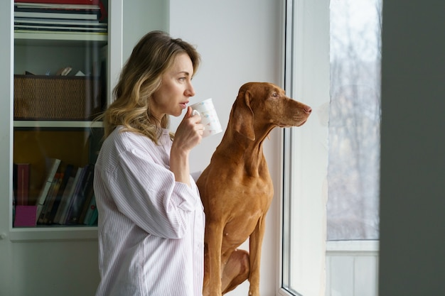 幸せな女性の所有者と窓越しに見ているコーヒーのカップを保持している窓辺に座っている犬