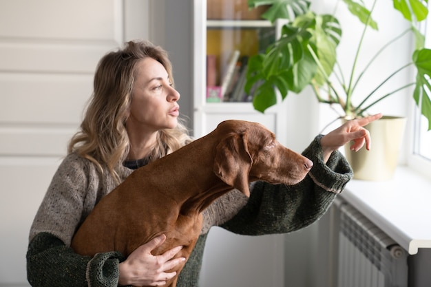 Happy woman owner and dog sitting on windowsill, holding cup of coffee, looking through the window