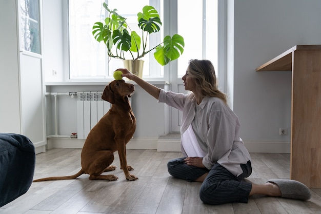집에서 테니스 공을 가지고 노는 그녀의 vizsla 강아지와 함께 행복한 여자 소유자, 바닥에 앉아