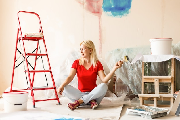Happy woman paint wall at home