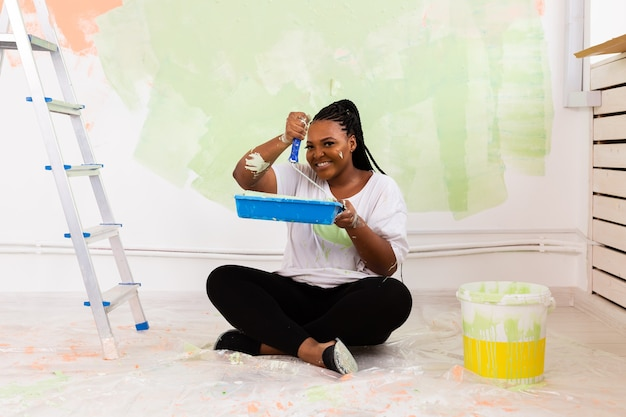 彼女の新しいアパートで壁を塗る幸せな女性