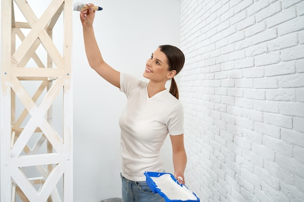 Happy woman painting wooden shelves at home