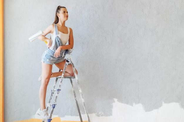 幸せな女は、自宅のローラーと梯子の上の壁を描画します。修理コンセプト