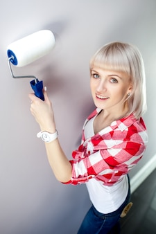 Happy woman paints wall with roller at home