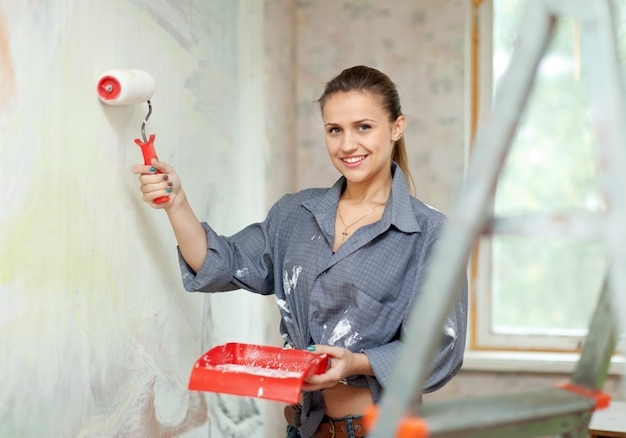 Happy woman paints wall