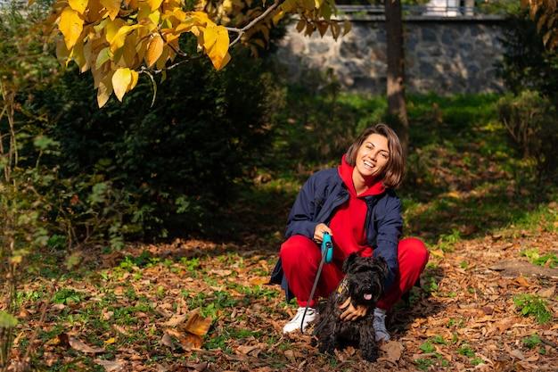 Donna felice nel parco con foglie autunnali