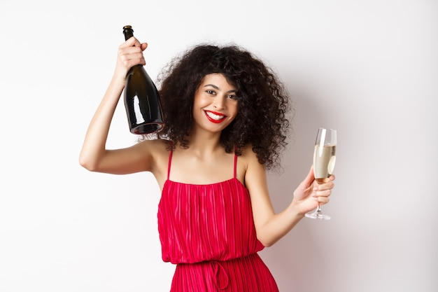 バレンタインデーの休日にパーティー、ガラスとシャンパンのボトルで踊る、赤いドレスを着て、白い背景に笑みを浮かべて幸せな女性。