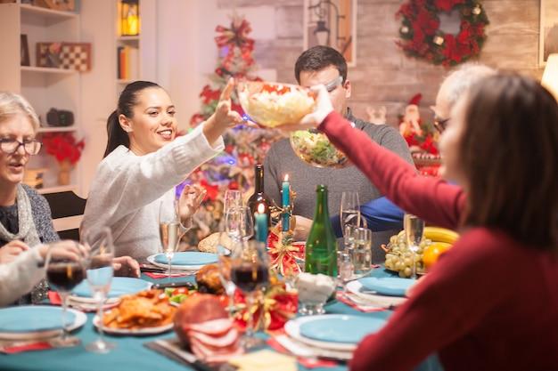 クリスマスの家族の夕食で彼の娘にテーブルの上にサラダを渡す幸せな女性。