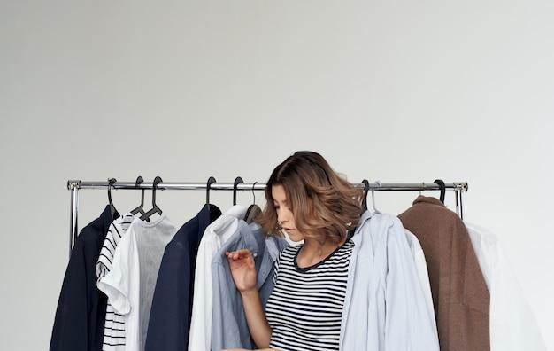 Счастливая женщина, выглядывающая из-за одежды в раздевалке, шоппинг молодежи