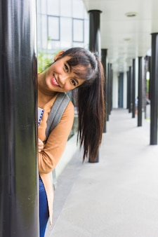 Happy woman peeping out from column