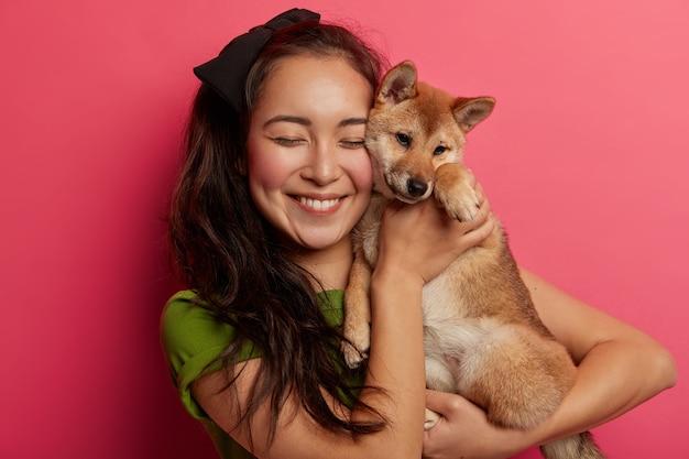 Il proprietario dell'animale domestico della donna felice tiene il cane sveglio vicino al fronte, trasporta il cucciolo di shiba inu, sorride piacevolmente, gode del momento dolce, isolato sopra fondo rosa.