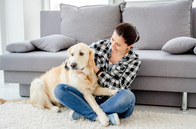 Счастливая женщина, лаская милую собаку в светлой квартире