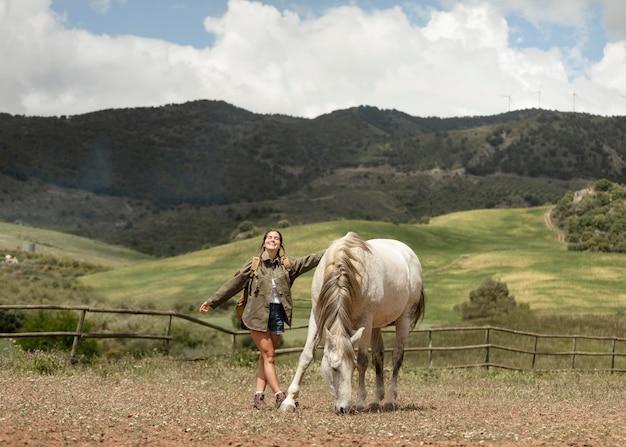Happy woman petting horse full shot