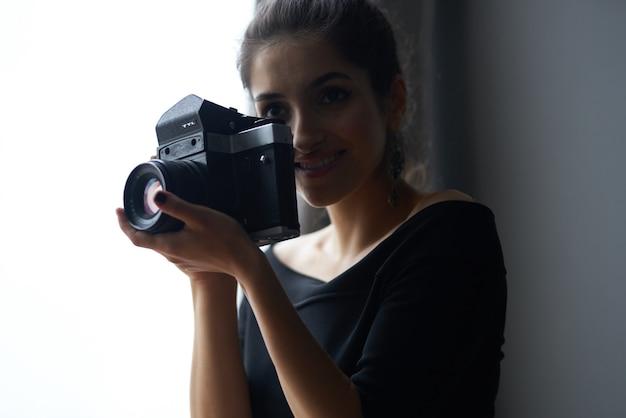 Happy woman photographer indoors silhouette model evening dress