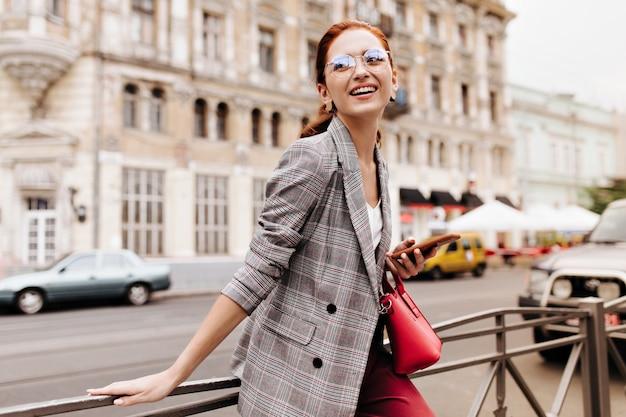 Donna felice in giacca a quadri sorridente e tenendo il telefono